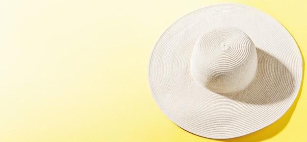 Straw hat on bright yellow sunny background Free Photo