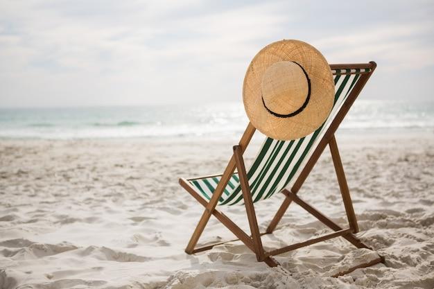 Straw hat kept on empty beach chair Free Photo