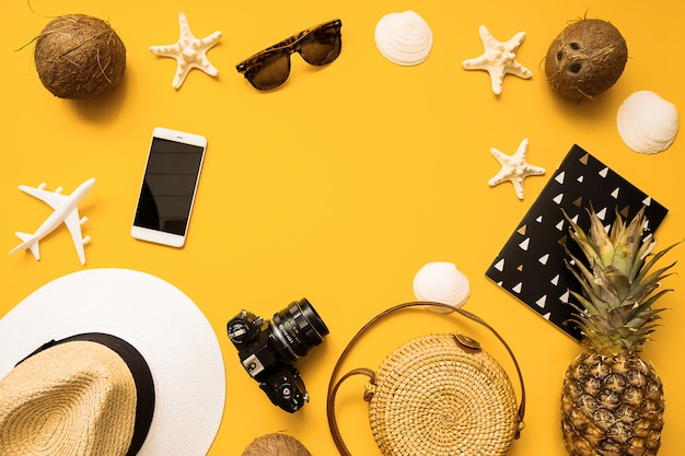 Straw hat, retro film camera, bamboo bag, sunglasses, coconut, pineapple, sea shells and starfish, air plane, notebook and phone Premium Photo