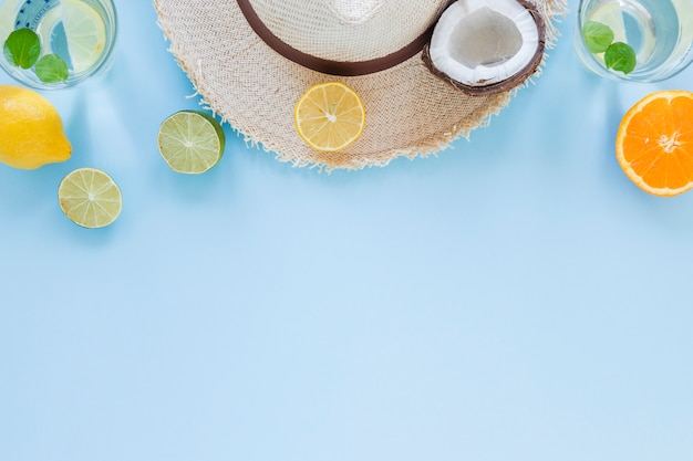 Straw hat with exotic fruits on table Free Photo