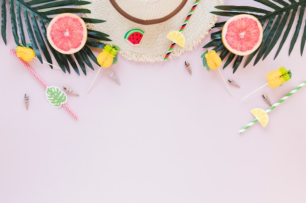 Straw hat with grapefruits and palm leaves Free Photo