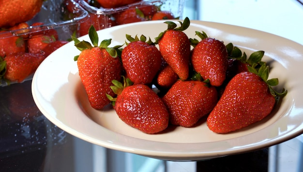 Strawberries are beautifully arranged  on a white plate