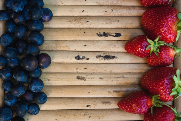 Strawberries and blueberries opposite each other on wooden surface Premium Photo