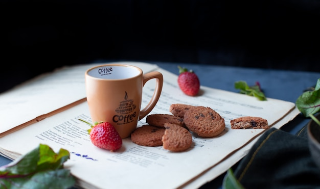 Strawberries, cookies and coffee cup on a book paper. Free Photo