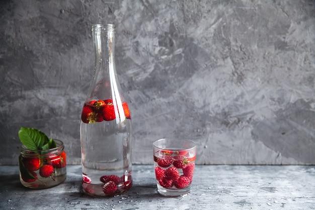 暗い灰色の背景の上に水のイチゴ。健康食品、フルーツ。装飾としての花の花束 Premium写真