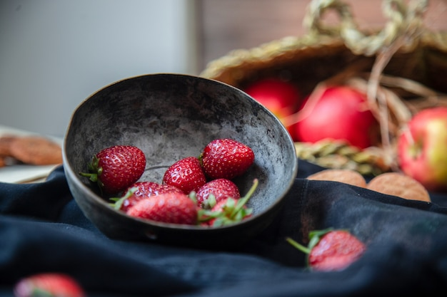 Strawberries inside bowl, cookies and apple basket on a black mat, blurred basket. Free Photo