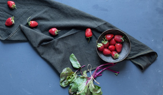 Strawberries inside bowl and leaves on a black mat. Free Photo