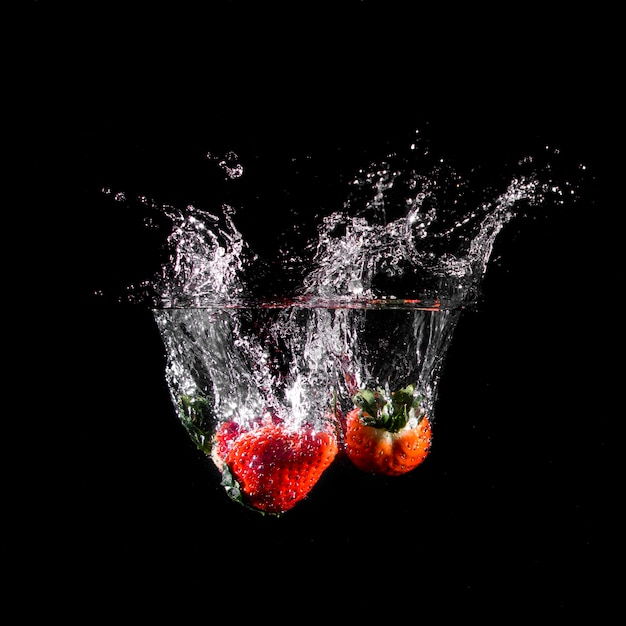 Strawberries plunging into the water Free Photo