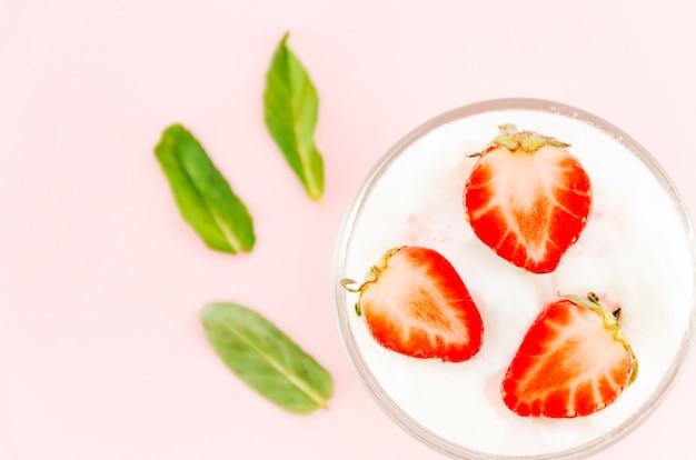 Strawberries with yogurt and green leaves Free Photo