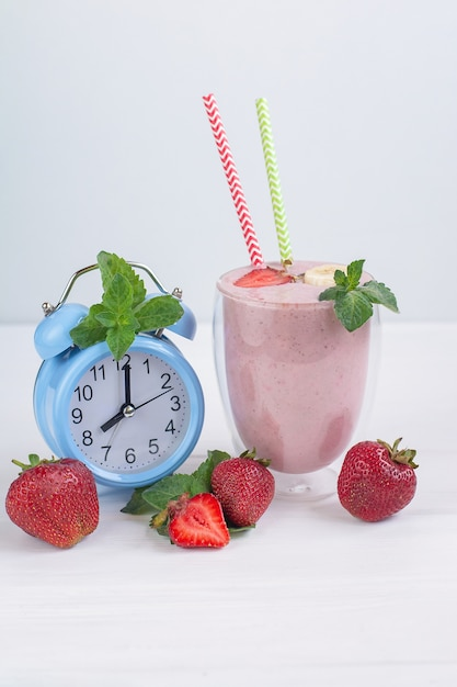 Strawberry and banana healthy smoothie with fresh strawberrys in glass decorated with mint. Premium Photo