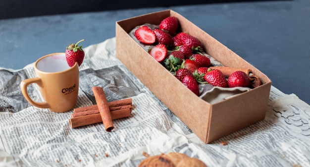 Strawberry carton box with cup and cinnamons on a newspaper. Free Photo