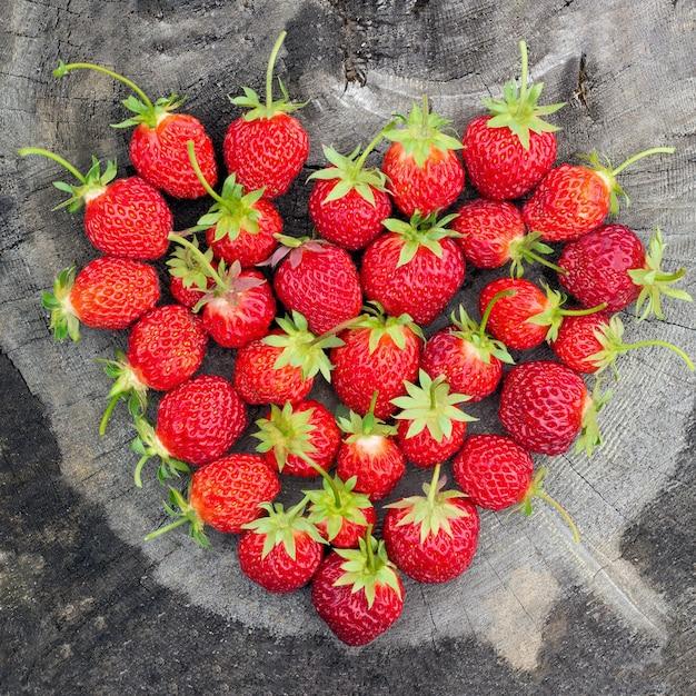 Strawberry heart shape on old cracked stump Premium Photo