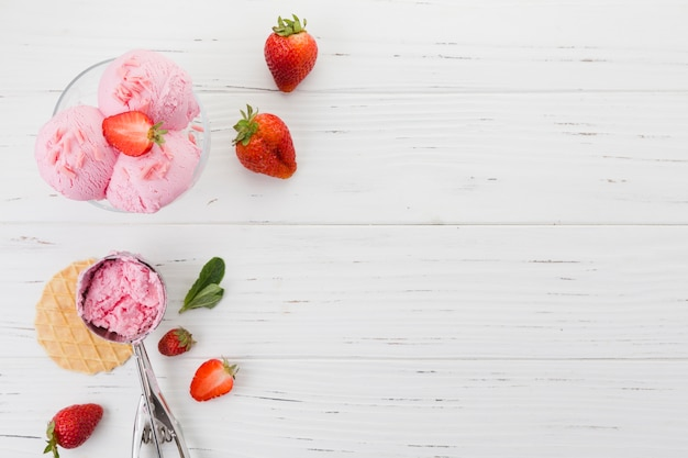 Strawberry ice cream in bowl on wooden surface Free Photo