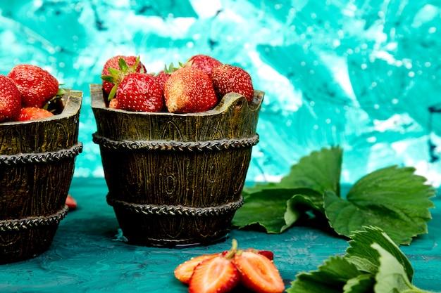 緑の背景にボウルにイチゴ。 Premium写真