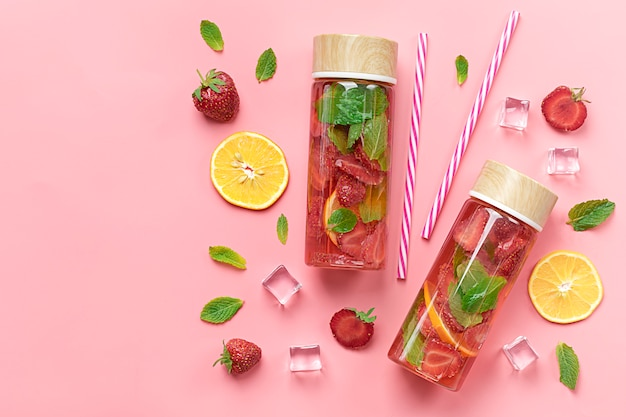 Strawberry infused water, summer iced drink with strawberry, lemon and leaf of mint on pink background Premium Photo