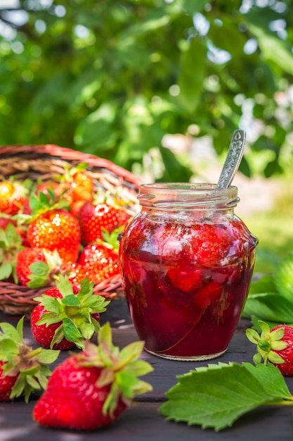 Strawberry jam and juicy ripe strawberries on a wooden table in the garden on a summer sun Premium Photo