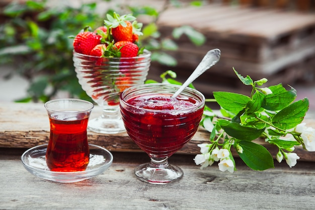 Strawberry jam in a plate with spoon, tea in glass, strawberries, plant side view on wooden and yard table Free Photo