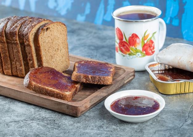 茶色のパンのスライスとお茶のカップとイチゴジャム。 無料写真