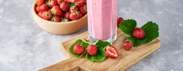 Strawberry milk shake in a glass jar and fresh strawberries with leaves, long banner Premium Photo