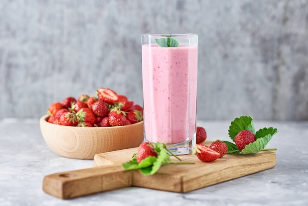 Strawberry milk shake in a glass jar and fresh strawberries with leaves Premium Photo