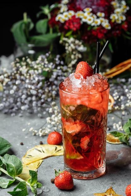 いちごモヒート。テーブルの上のグラスにイチゴ、ミント、レモン、氷と冷たい夏のモヒートカクテル。 Premium写真
