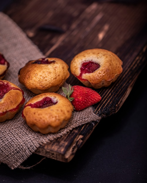 Клубничный кекс и кофейные зерна на деревянной доске на столе темного дерева Premium Фотографии