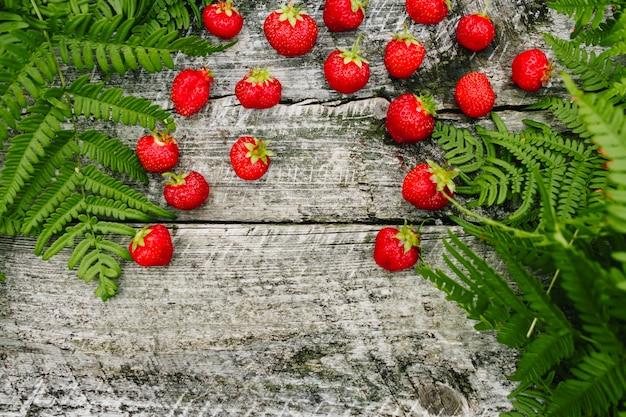 木製の灰色の背景、シダの葉、イチゴの季節のイチゴ Premium写真