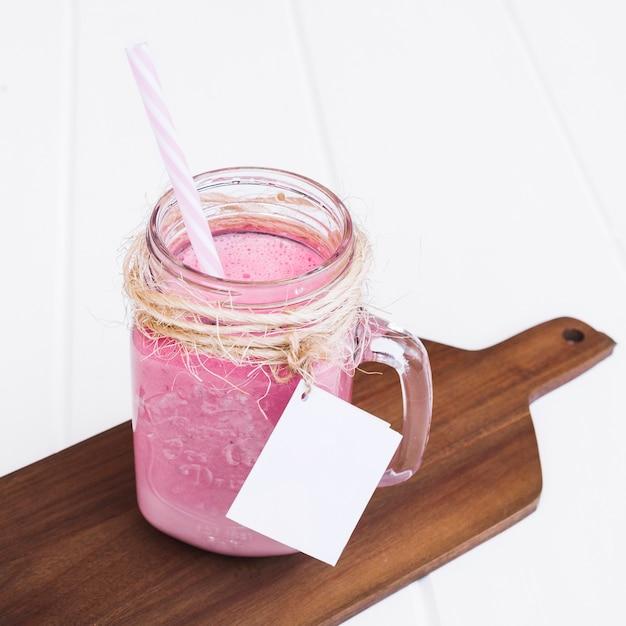 Frullato di fragole con paglia e etichetta per mock up su tavola di legno Foto Gratuite
