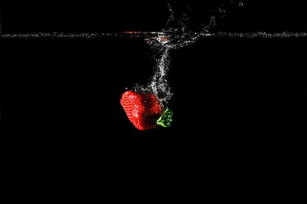 Strawberry in water with black background. Premium Photo