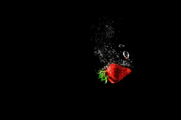 Strawberry in water with black. Premium Photo