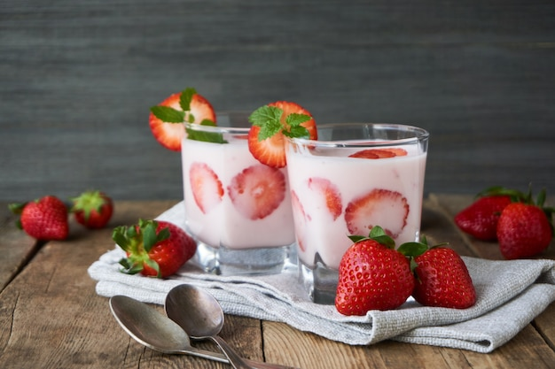Strawberry yogurt in a glass on a wooden table Premium Photo
