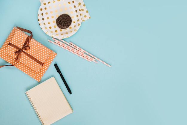 Straws and present between muffin and notebook Free Photo