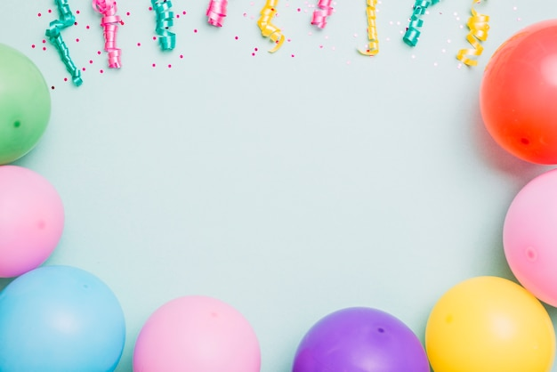 Streamers and colorful balloons on blue backdrop with space for text Free Photo