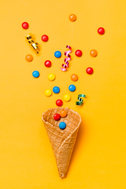 Streamers and gems on waffle against yellow background Free Photo