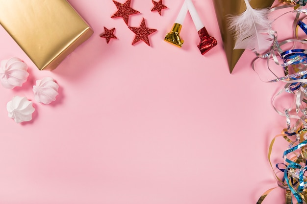 Streamers; star stickers; gift box; party hat; feather; zephyrs and party blowers on pink backdrop Free Photo