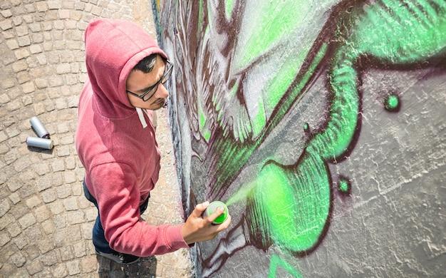 Уличный художник, рисующий красочные граффити на общей стене - высокий угол обзора Premium Фотографии