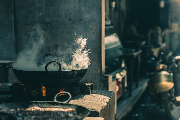 Street food in india cooking in fatiscent big pan or wok in a small street food stall. Premium Photo