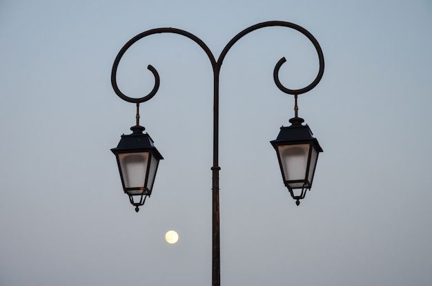 Street lamp in the evening on a background of the moon on the coast of greece (heraklion) Premium Photo