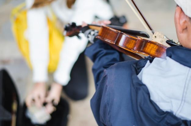 Уличный музыкант играет на скрипке Premium Фотографии