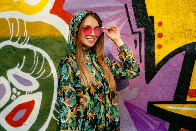 Street photo of beautiful girl in red eyeglasses and hood. dressed up in green colorful jacket Free Photo