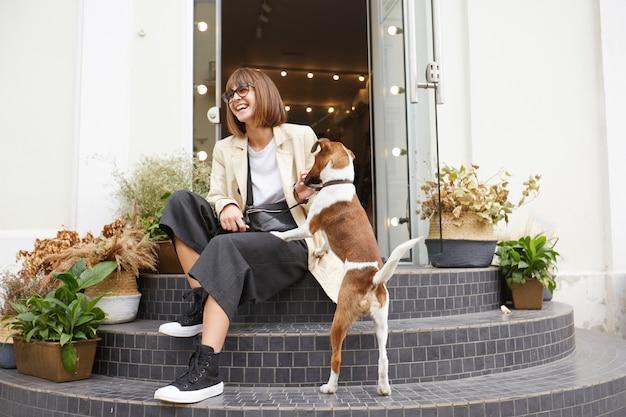 近くの階段に座っている魅力的な女性のストリート写真は、彼女の素敵な犬のジャックラッセルテリアです。 無料写真