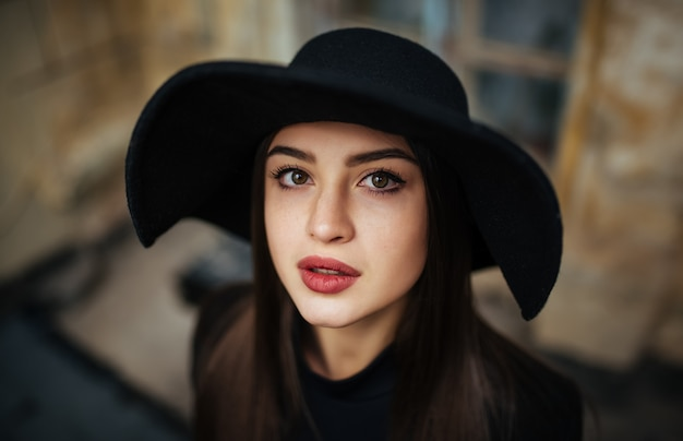 Street portrait of young casual lady in hat, black clothes, red lips Free Photo