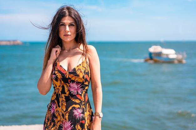 ストリートスタイル、美しい花柄のドレスを着たスリムな若いブルネットと海を背景にした帽子の肖像画 Premium写真
