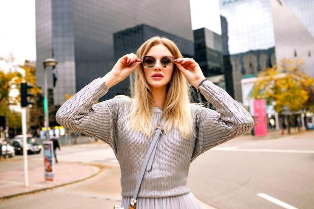Уличный стильный портрет блондинки, носящей гламурный серый наряд, положил руку на ее солнцезащитные очки, район бизнес-центра. Бесплатные Фотографии