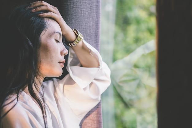 Stress asian woman having headache next to the window Premium Photo