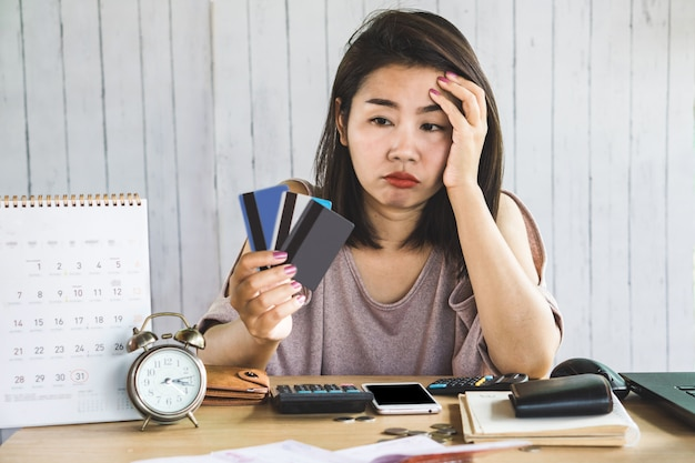 Stress asian woman looking at credit cards in hand Premium Photo