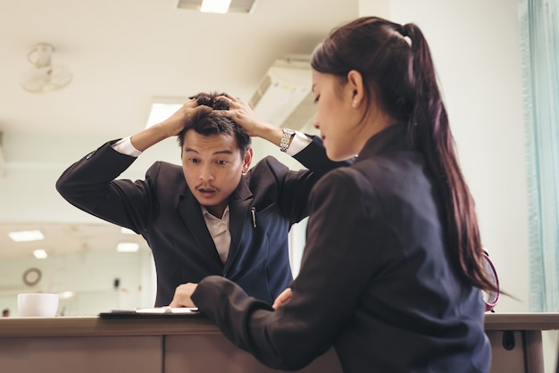Stress businessman with hand holding head while negotiations with businesswoman, Premium Photo