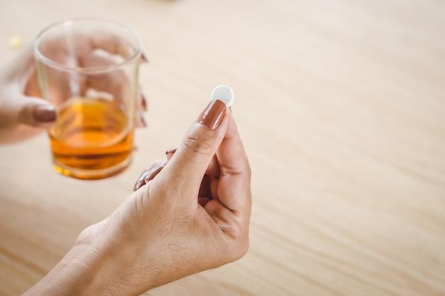 Stress woman taking medicine with alcohol Premium Photo