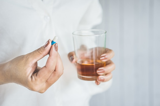 Stress woman taking sleeping pill with alcohol Premium Photo
