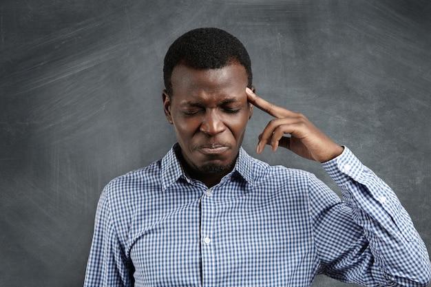 Sottolineato uomo d'affari africano con un'espressione meticolosa che lotta per ricordare qualcosa, chiudendo gli occhi e premendo un dito sulla tempia come se avesse un forte mal di testa. Foto Gratuite